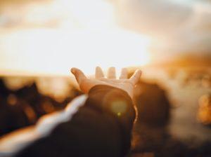 光に手を伸ばす女性のイメージ