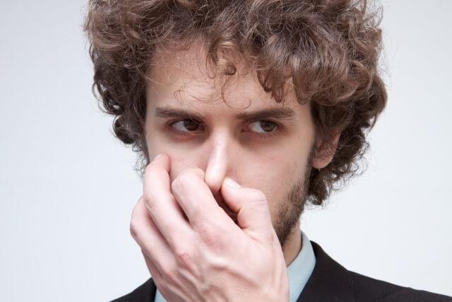 鼻をつまむ男性のイメージ画像